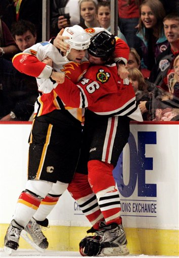 Calgary Flames' Mark Giordano, left, fights with Chicago Blackhawks' Colin Fraser during the first period of an NHL hockey game Sunday, Jan. 4, 2009, in Chicago. (AP Photo/Nam Y. Huh)